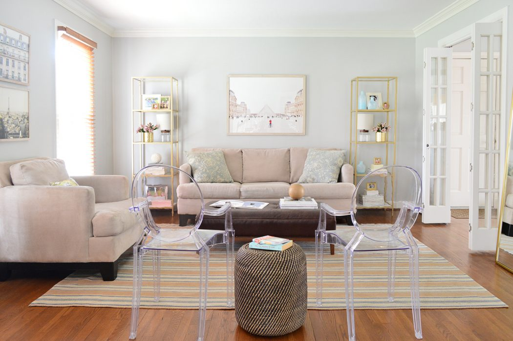 neutral living room decorated with shelves artwork and lots of seating