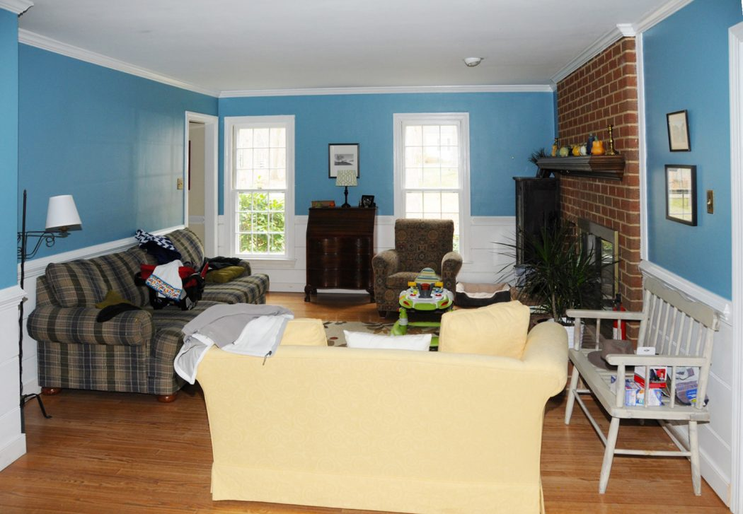 living room before staging with blue walls brick fireplace and lot of furniture