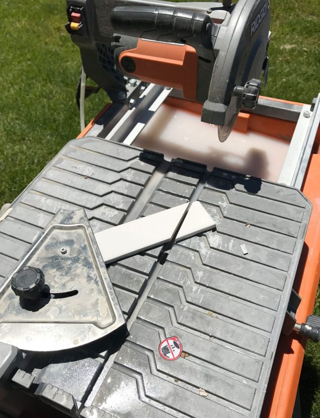 wet saw being used to cut a 45 degree angle on single subway tile