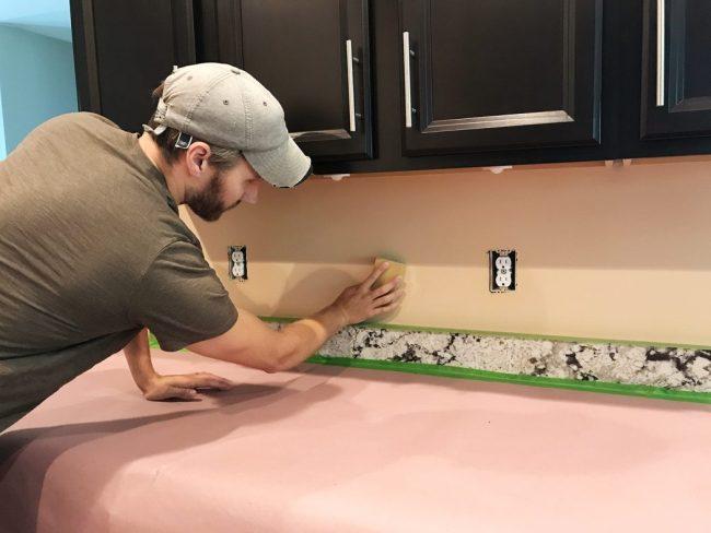John sanding backsplash wall in preparation for tile installation