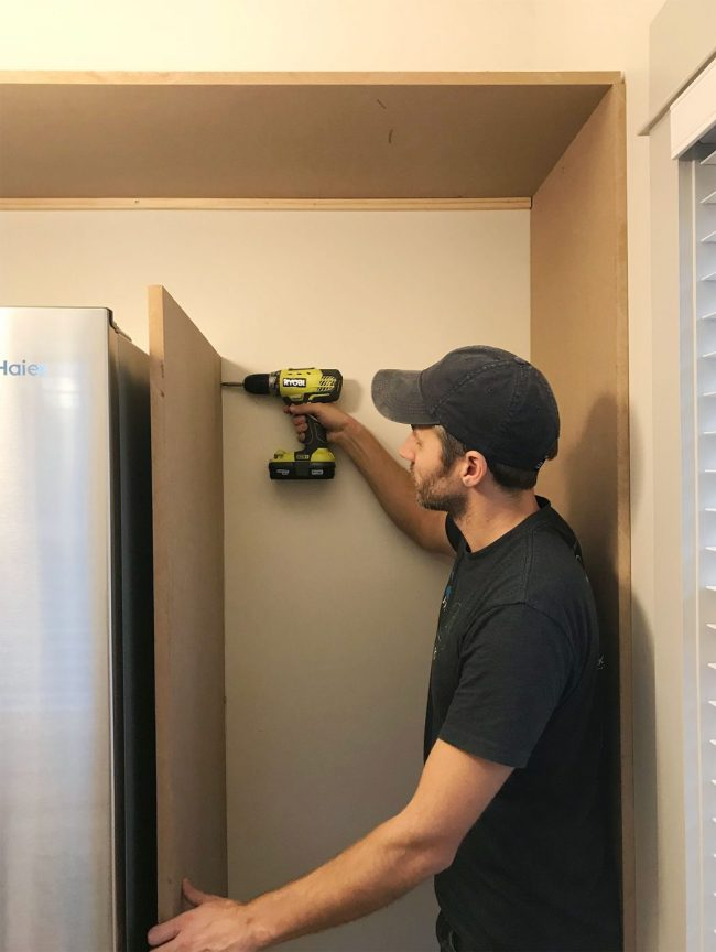 John drilling vertical MDF panel into wood already placed near fridge in pantry
