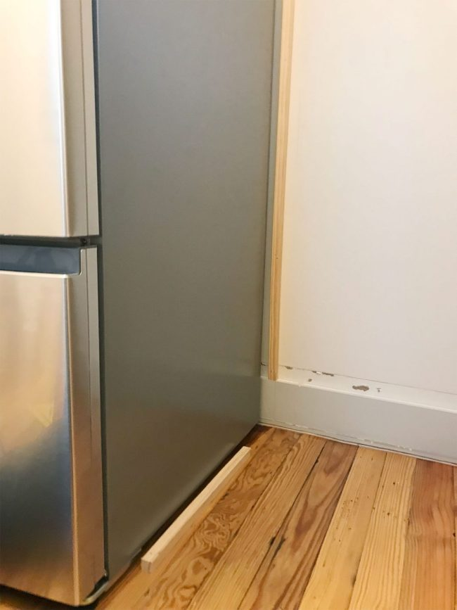 thing pieces of wood installed near fridge on wall and floor