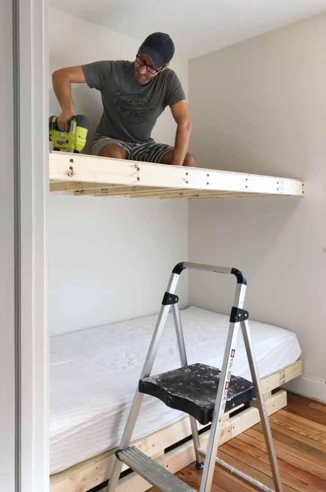 John sitting on top bunk to nail plywood into floating platform
