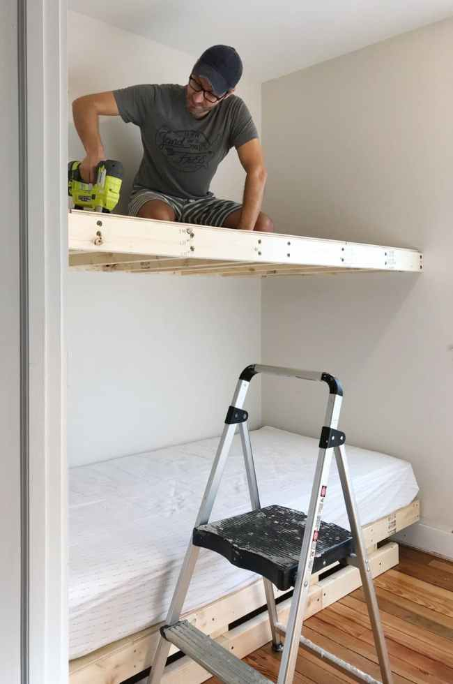 John sitting on top bunk to nail plywood into floating platform