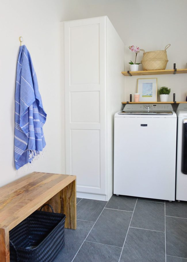 wood bench in front of laundry room storage with towel hook