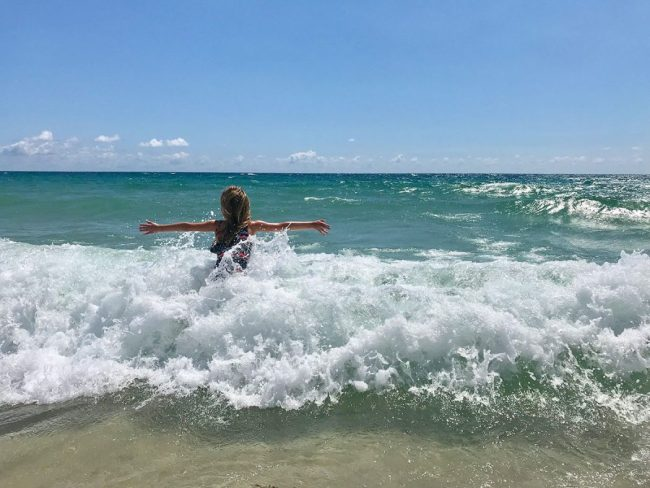 little girl playing in waves during Spring Break in Lauderdale By The Sea Florida