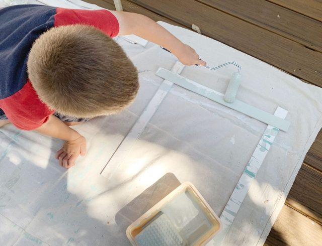 Young Boy Painting Wood Piece With Small Foam Roller