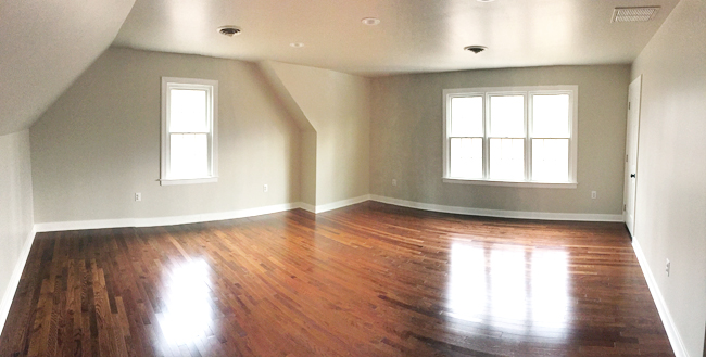 Wide angle panoramic photo of an empty bonus room with tan walls, wood floor, windows, and niche nook