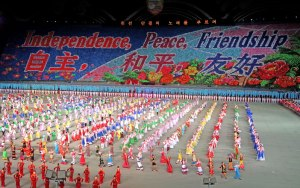 Gymnasts perform under the heading 'independence, peace, friendship' in Chinese and Korean