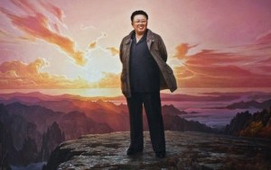 A large portrait of Kim Jong ll standing atop Mount Paektu at sunset.