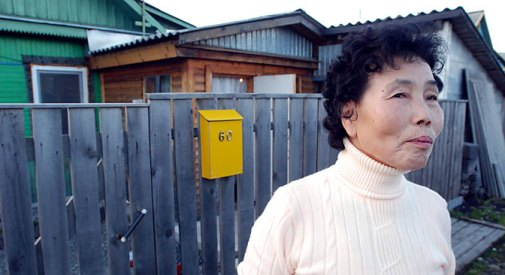 An ethnic Korean lady standing in front of her house on Sakhalin Island.