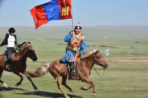 A Mongolian horseman rides past with the flag of Mongolia in the run-up to a Mongol horse race.