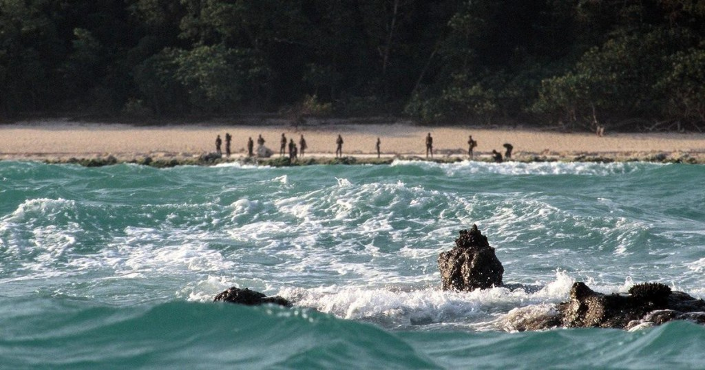 Worst islands: several North Sentinelese tribespeople stand on the beach of North Sentinel Island, looking out to sea.