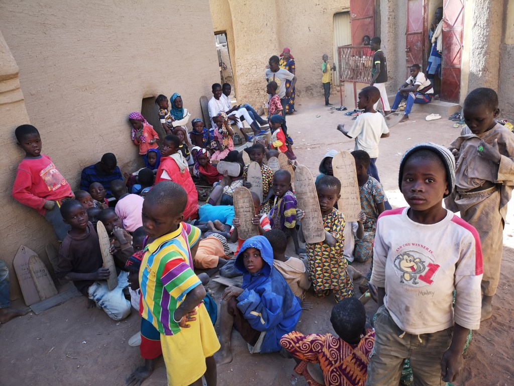 kids studying outside at a local madrassa in Djenné, Mali
