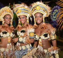 Three women in flamboyant costumes pose at the Angola Carnival.