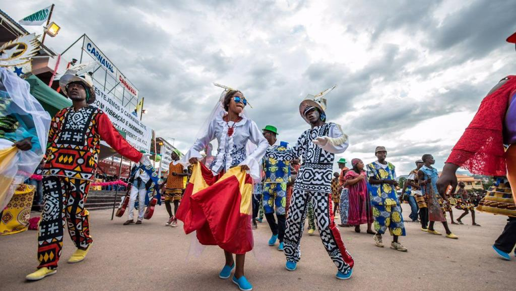Revellers in colourful costumes dance under a cloudy sky at the Angolan Carnival.
