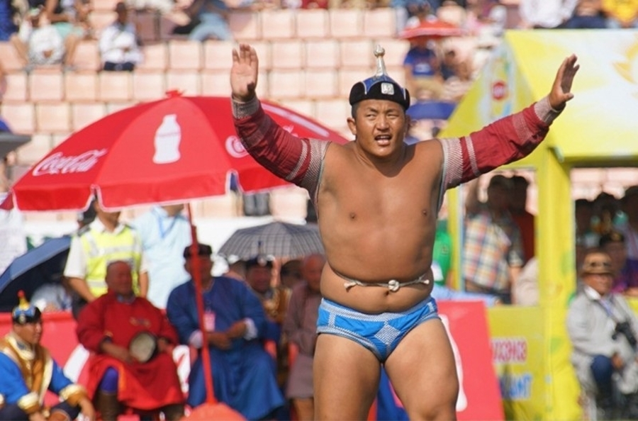 A stocky Mongolian wrestler in traditional wrestling trunks prepares to fight.