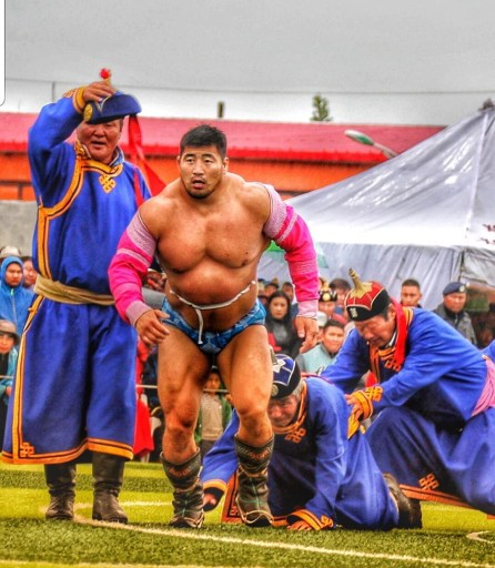 Mongolian people: a muscular Mongolian wrestler strides towards the starting point for his bout.