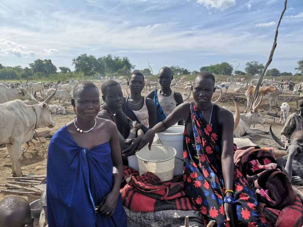 Mundari girls sitting by Terekeka Cattle Camp in South Sudan