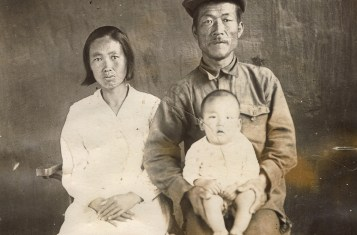 An ethnic Korean father and mother with their infant child pose in this sepia picture.