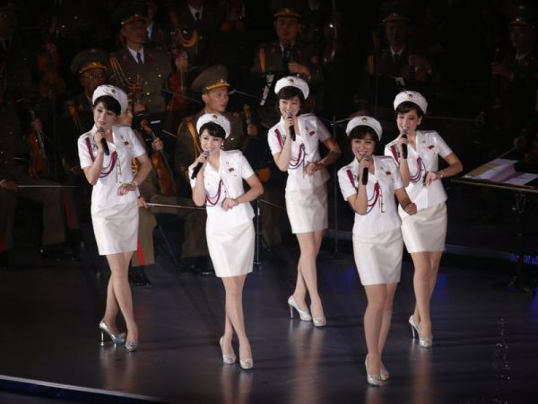 Five members of the Moranbong Band in white military uniforms performing on stage.