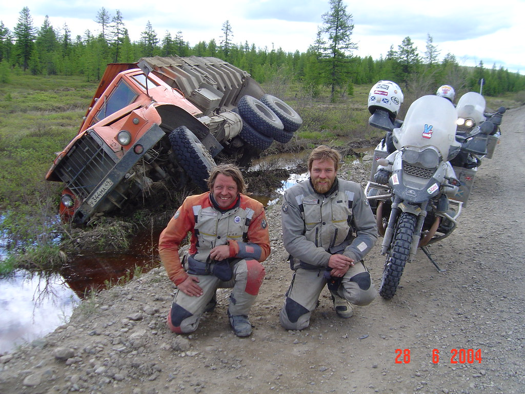 Two men pose alongside motorcycles on the Road of Bones.