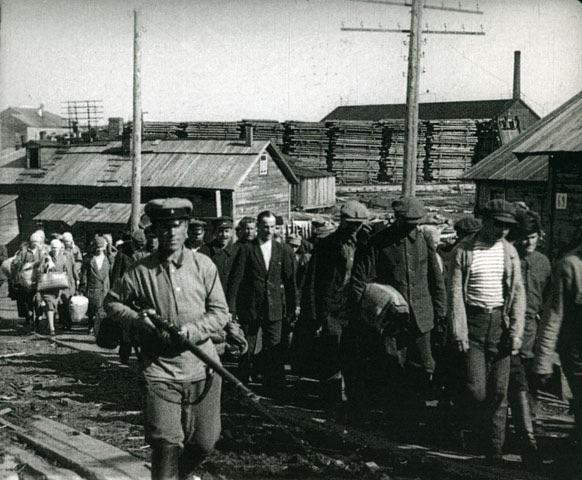 A black and white image of Soviet deportees being escorted by armed guards.