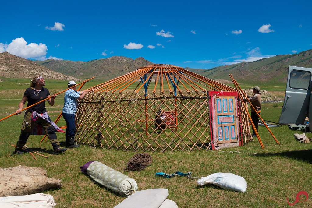 Several people work together to erect a Mongolian ger.