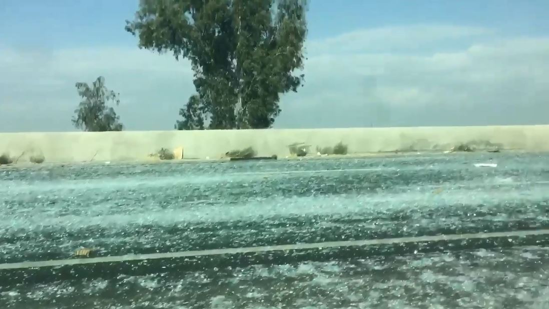 Broken glass covering section of Highway 99, traffic backed