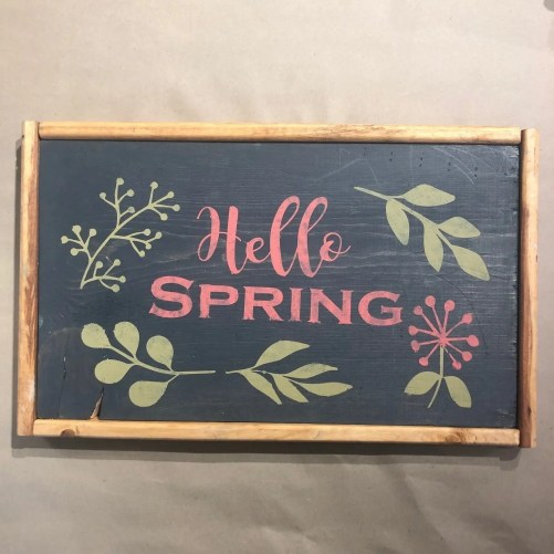 Framed wood sign with the phrase Hello Spring along with a variety of leaves and flowers