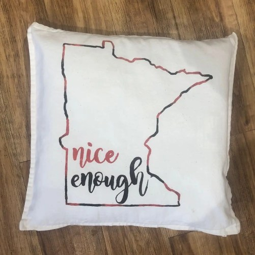 Pillow with an outline of the state of Minnesota and the phrase nice enough on the inside.