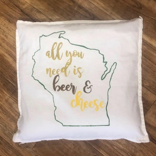 Pillow with the outline of the state of Wisconsin and the phrase All you need is beer and cheese