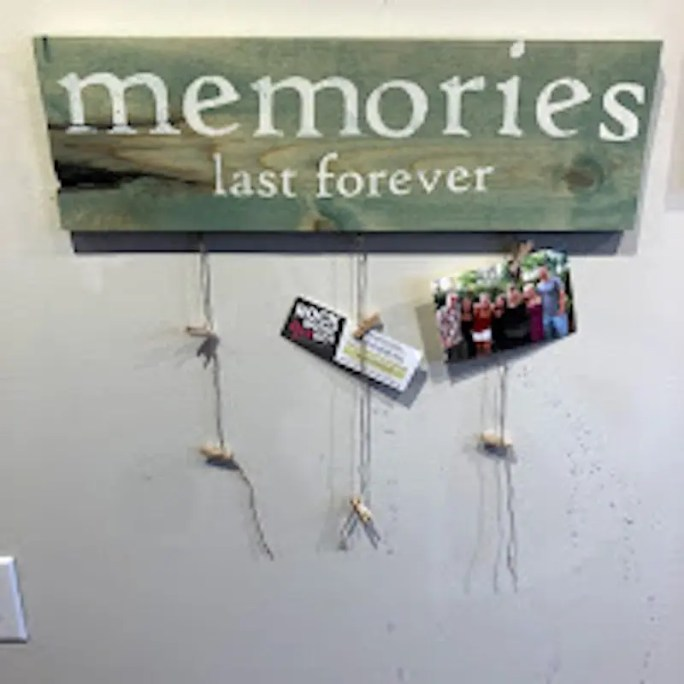Wood sign with the phrase meories last forever and string with clothespins to clip pictures to