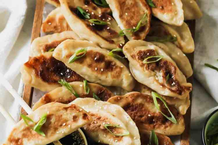 Chicken Dumplings on a wooden tray with chopsticks, scallions, and sesame soy dippings sauce.