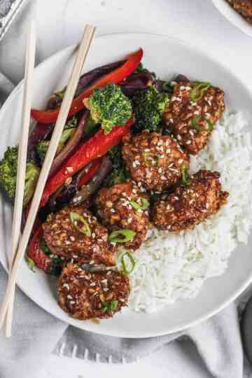 Close up of air fryer almond chicken in honey soy sauce with stir fried veggies, chopsticks, and white rice.