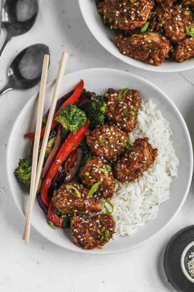 Crispy chicken in honey soy sauce in a bowl with stir fried veggies and white rice with chopsticks and sesame seeds on the side.