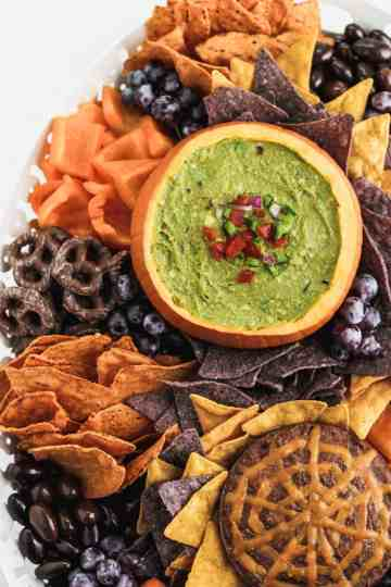 Halloween guacamole snack board on a large white platter.