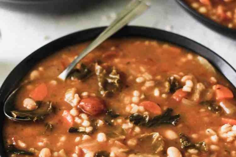 One pot vegetable, bean, and barley soup in 3 black bowls with a silver spoon.