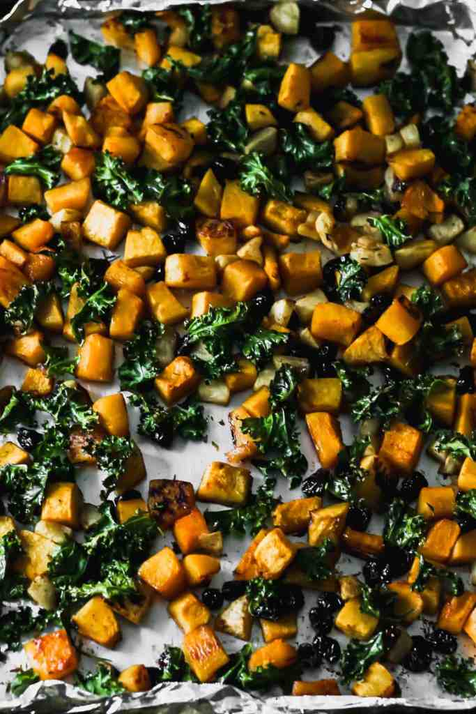 Roasted butternut squash, apples, cranberries, and kale on a foil lined sheet pan.