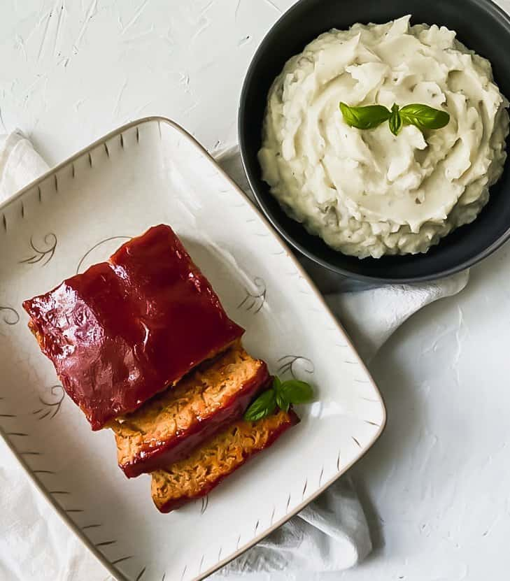 Healthy chicken meatloaf on a white serving platter with a side of mashed potatoes in a black bowl.