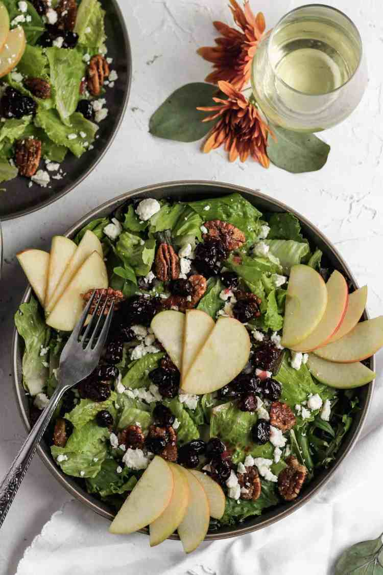 Apple cranberry salad in a black bowl with a silver fork, glass of white wine, and orange flowers.