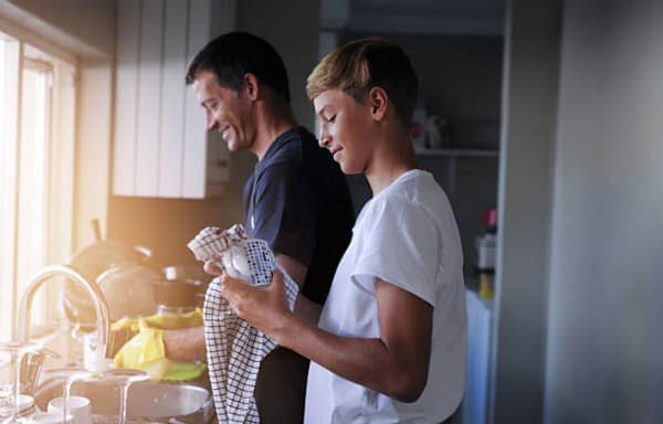 Child doing chores with dad  standing in a kitchen