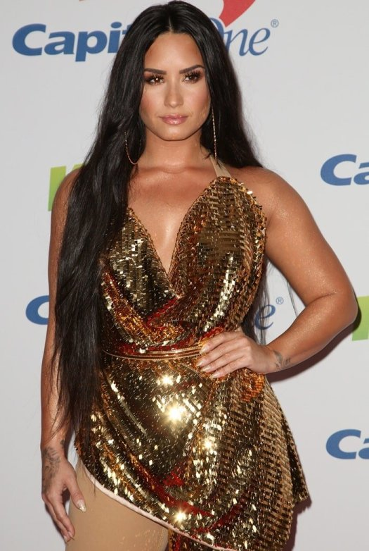 Demi Lovato's monstrous Frolov Spring 2018 gold jumpsuit featuring one beige pant leg and an embellished counterpart