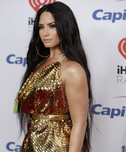 Demi Lovato's makeup by Jill Powell was golden bronze while her long dark hair was parted down the middle