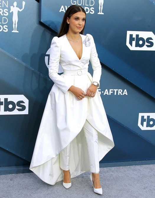 Millie Bobby Brown shows a glimpse of cleavage in Louis Vuitton white dress suit