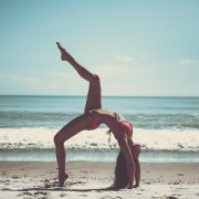 girl doing yoga on the beach