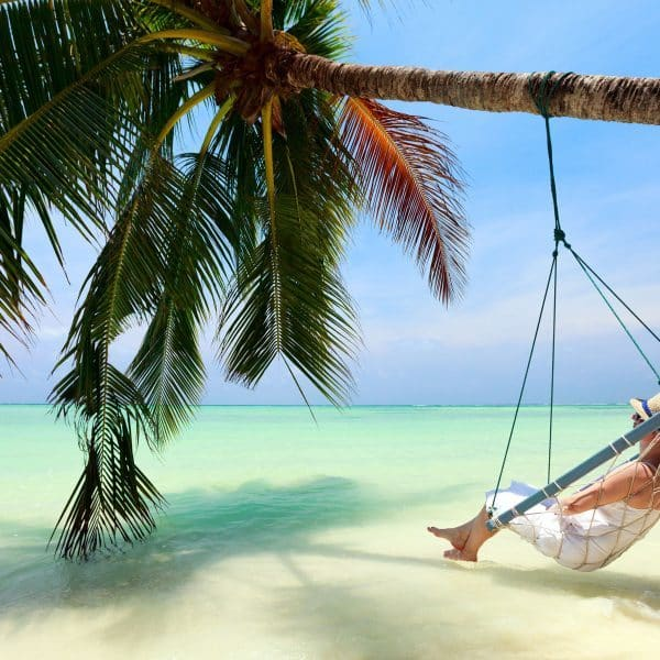 Woman in swing under palm tree with ocean view arrange with luxury travel agents