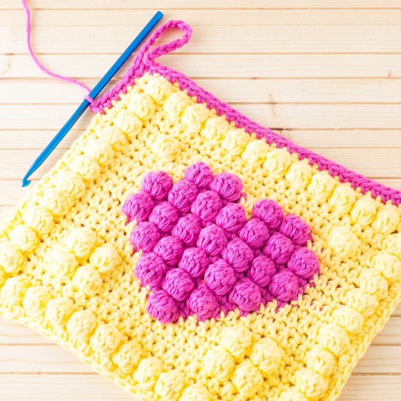 in-progress view of the border of the bobble heart potholder, as it's being crocheted
