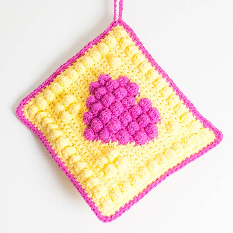 pink and yellow bobble heart potholder hanging against a white background