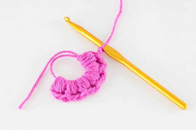 six puff stitches in a magic ring with pink yarn and a gold crochet hook